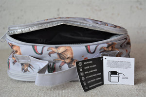 A MontiiCo insulated lunch bag in the 2020 dinosaur design which has brown triceratops and green and red velociraptor dinosaurs o a grey slate background. This picture shows the back pocket open which is a separate compartment for the included ice pack.