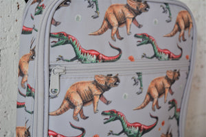 A MontiiCo insulated lunch bag in the 2020 dinosaur design which has brown triceratops and green and red velociraptor dinosaurs o a grey slate background. This is a close up view of the lunch bag and shows the design and front picket zipper