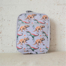 Load image into Gallery viewer, A MontiiCo insulated lunch bag in the 2020 dinosaur design which has brown triceratops and green and red velociraptor dinosaurs o a grey slate background. This is a front view of the lunch bag.