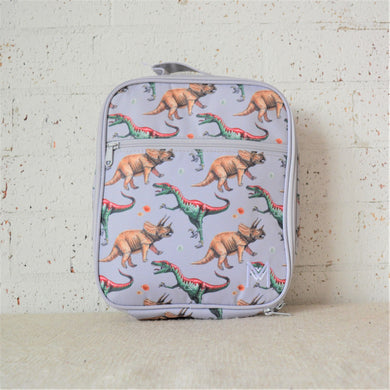 A MontiiCo insulated lunch bag in the 2020 dinosaur design which has brown triceratops and green and red velociraptor dinosaurs o a grey slate background. This is a front view of the lunch bag.