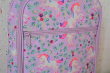 Load image into Gallery viewer, A MontiiCo insulated lunch bag for school kids that has a unicorn design. It has white unicorns with pink and purple hair, as well as purple flowers and green leaves on a light purple background.  This is a close up view of the zipper on the front pocket and the design.