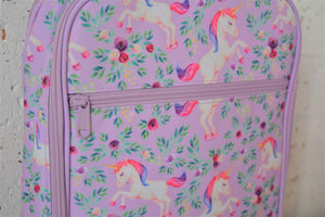 A MontiiCo insulated lunch bag for school kids that has a unicorn design. It has white unicorns with pink and purple hair, as well as purple flowers and green leaves on a light purple background.  This is a close up view of the zipper on the front pocket and the design.