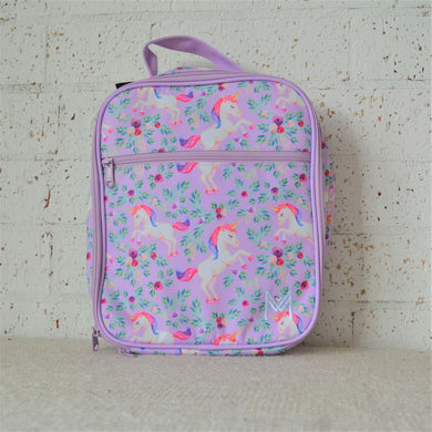 A MontiiCo insulated lunch bag for school kids that has a unicorn design. It has white unicorns with pink and purple hair, as well as purple flowers and green leaves on a light purple background.  This is the front view.