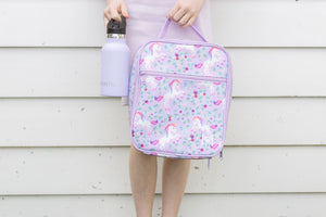 A child holding a MontiiCo insulated lunch bag for school kids that has a unicorn design. It has white unicorns with pink and purple hair, as well as purple flowers and green leaves on a light purple background.  They are also holding a MontiiCo Mini drink bottle in lavender.