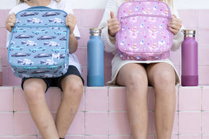 Two kids sitting next to each other. The child on the right is holding a MontiiCo insulated lunch bag in a fairy print which has fairies with a pink dress and pink wings and brown hair in a bun, blue birds flying, pink bows and pink hearts on a pink background. The child on the left is holding a MontiiCo insulated lunch bag in a blue cars design.