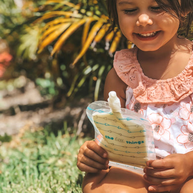 A young happy girl sits down on the grass with her yoghurt in a Sinchies resusable food pouch.