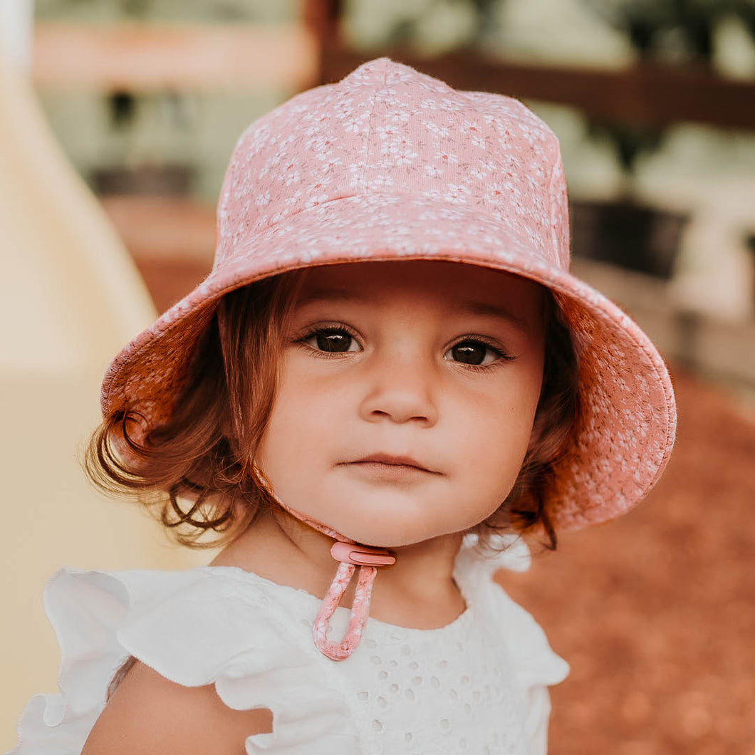Bedhead hats. Bedhead toddler bucket hat in Sophia, with white flowers on a pink background. This print is from the Bedhead hats Winter 2021 collection and sold by Gumnut Kids, online Bedhead hat stockist in Berowra, NSW.