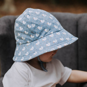 A toddler wearing a blue bucket hat with white ducks on it made by Bedhead hats Australia