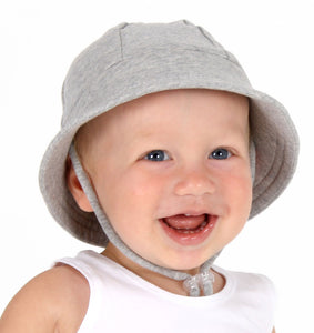 a smiling baby boy wearing a grey bucket hat made by bedhead hats