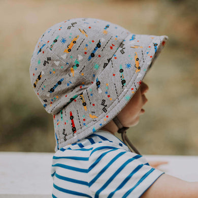 A little boy wearing a greay bucket hat that has a chin strap and speed cars on it. They are blue, yellow, green and red and there is also flags and other racing related images on the design. It is made by Bedhead hats and this is the side view showing the excellent sun protection