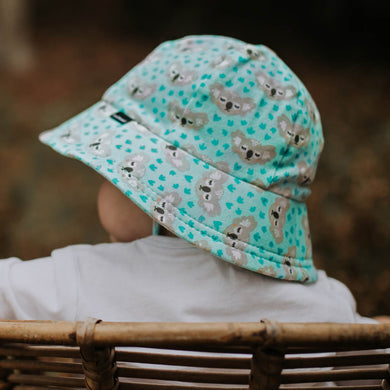 A toddler wearing a Bedhead bucket hat in koala print. The hat has an aqua green background with sleepy koala faces on the design and green koala footprints.
