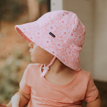 Load image into Gallery viewer, the side of a baby girl wearing a pink daisy bucket hat made by bedhead hats