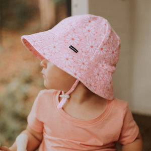 the side of a baby girl wearing a pink daisy bucket hat made by bedhead hats