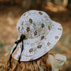 A girl wearing a linen panelled bucket sun hat with a light grey background and white flowers with a black outline made by bedhead hats in the heritage collection. this picture shows a drawstring at the back that you can use to adjust the size of the hat