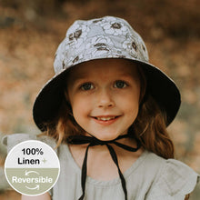 Load image into Gallery viewer, A girl wearing a linen panelled bucket sun hat with a light grey background and white flowers with a black outline made by bedhead hats in the heritage collection