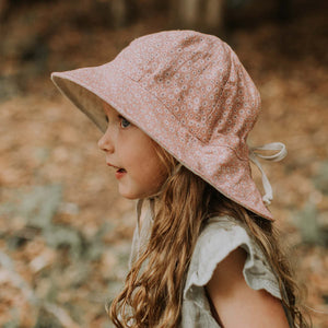 A young girls wearing a linen panelled bucket hat with small white daisies on a subtle pink background made by Bedhead hats in the heritage collection. You can see a drawstring at the back that allows you to adjust the size of the hat