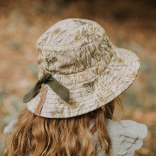 Load image into Gallery viewer, A girl wearing a linen sun hat with a beautiful Australiana design of green and olive mallee eucalyptus leaves on a neutral cream background. This picture shows the back view with an olive drawstring to adjust the size