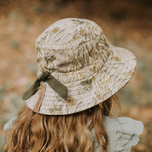 A girl wearing a linen sun hat with a beautiful Australiana design of green and olive mallee eucalyptus leaves on a neutral cream background. This picture shows the back view with an olive drawstring to adjust the size
