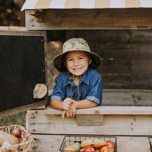 Load image into Gallery viewer, A boy wearing a linen sun hat with a beautiful Australiana design of green and olive mallee eucalyptus leaves on a neutral cream background