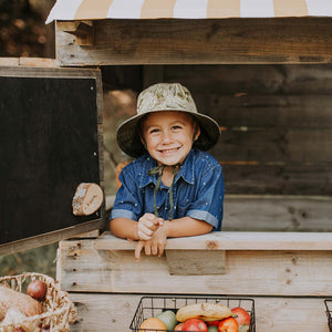 A boy wearing a linen sun hat with a beautiful Australiana design of green and olive mallee eucalyptus leaves on a neutral cream background