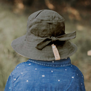back view of a boy wearing a bedhead reversible linen bucket hat in an olive green colour