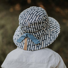 Load image into Gallery viewer, A boy wearing a linen bucket sun hat that has a denim blue background and white striped with dots on them made by Bedhead hats this is the back view showing a drawstring that you can use to adjust the size