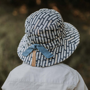 A boy wearing a linen bucket sun hat that has a denim blue background and white striped with dots on them made by Bedhead hats this is the back view showing a drawstring that you can use to adjust the size