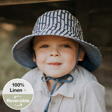 Load image into Gallery viewer, A boy wearing a linen bucket sun hat that has a denim blue background and white striped with dots on them made by Bedhead hats