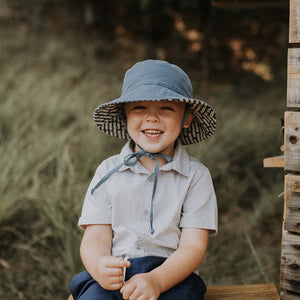 A boy wearing a linen bucket hat in steele blue made by bedhead hats