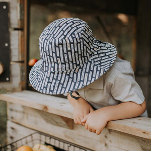 A boy wearing a linen bucket sun hat that has a denim blue background and white striped with dots on them made by Bedhead hats this is the top view