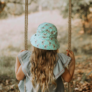 a girl on a swing wearing a kids bucket hat that has grey koala faces and green footprints on a green background
