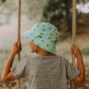 a boy on a swing wearing a kids bucket hat that has grey koala faces and green footprints on a green background