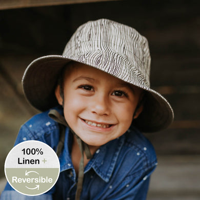 A young boy wearing a Bedhead heritage linen bucket hat in bark design that looks like scribbly gum bark of an Australian tree. The reverse side is a beautuful olive colour.