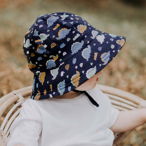 Bedhead Hats. Stegosaurus Dinosaur Bucket hat for toddler boys. Dark blue cotton stretch jersey fabric with blue and orange dinsoaurs. Bedhead hats are sold by Gumnut Kids, Sydney online stockist of Bedhead hats.
