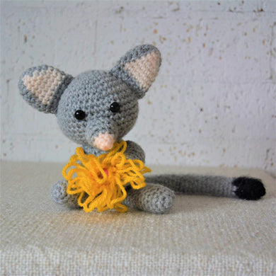 A handmade crochet toys that is an Australian brushtail possum animal. Is it crocheted mainly from grey yarm with has white ears and a white nose and a black tip on its bushy tail. It is holding a yellow gum blossom flower.