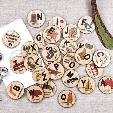 A set of 26 wooden Australian made alphabet discs that have pictures on Australian animals and icons on them as well as a letter of the alphabet each.