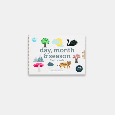A front view of the packaging of a set of Day, Month and Season Flash cards made by Two Little Ducklings. The pictures on the packaging include a tree, clouds and sun, a swan, a mountain and a tiger. The background is white.