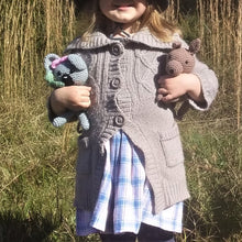Load image into Gallery viewer, A little girl is holding two handmade crochet Australian animals. One is a grey koala with a pink bow and the other is a brown kangaroo.