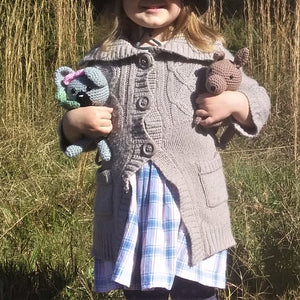 A little girl is holding two handmade crochet Australian animals. One is a grey koala with a pink bow and the other is a brown kangaroo.