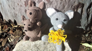 Two Australian animal toys sitting against a tree on a rock, on the left is a brown kangaroo and joey and on the right is a grey brushtail possum holding a yellow flower. Both toys have being handmade and are crochet.