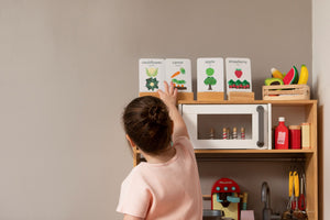 A playroom kitchen with a young girl plating with her Two Little Ducklings Fruit and Vegetable flash cards from Gumnut Kids, Berowra NSW.