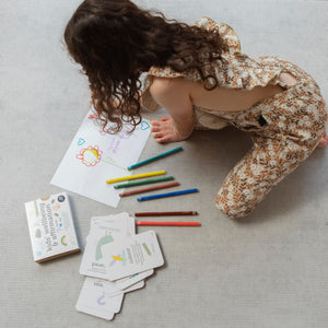 A girl drawing who has being inspired by her wellbeing and affirmations flash cards by Two Little Ducklings