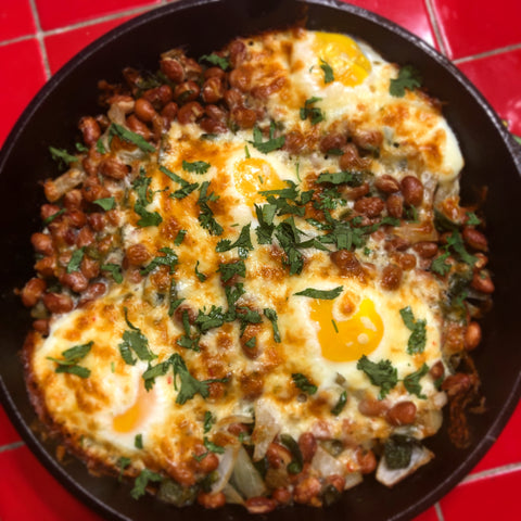 Breakfast Skillet with eggs beans and bacon in cast iron pan