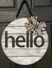 Hello Door Hanger is shown hanging on a front door.  This is the white distressed hanger with black beaded garland.