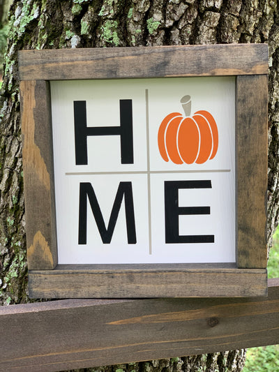 "Home (Pumpkin) Sign is shown sitting on a ladder outside.  This sign is all hand painted with an orange pumpkin for the ""o"".  Makes a great gift."