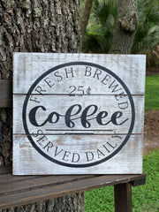 Fresh Brewed Coffee Pallet Board Sign is shown sitting outside on a ladder.  The white distressed pallet board has the black hand painted image on it.  Perfect for any coffee bar and all coffee enthusiast.