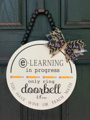 "E-Learning Door Hanger Sign shows the 12"" round sign with black beads and a bow attached.  This sign can be completely customized with colors and wording.  All sales are final."
