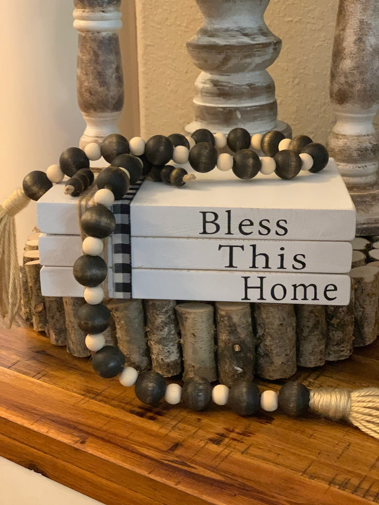 This image shows the large book set that is white and says Bless This Home.  It is shown with a beaded garland.  Each item is sold separately.