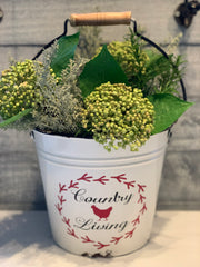 Country Living White Metal Pail is shown with a floral arrangement.  Flowers are not sold with bucket.