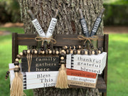 This image shows the Wooden Book Sets sitting on a ladder outside with a beaded garland and mini rolling pins.  Each item is sold separately.